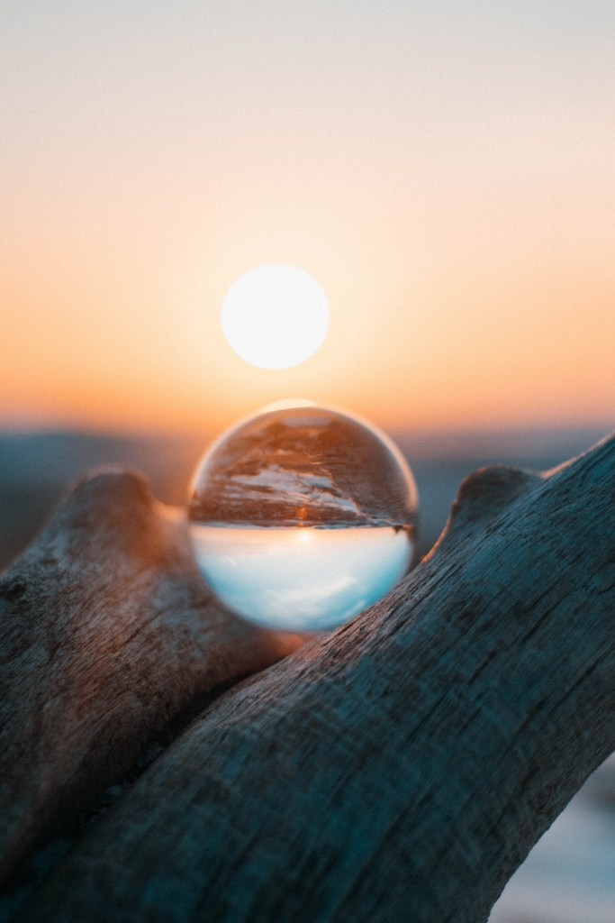 crystal ball in wood with sunset in background